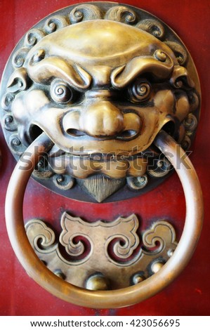 Close up of traditional Chinese lion door knocker on a red door - stock photo