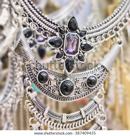 Close-up of traditional silversmith jewelry trimmed with black pearls - stock photo