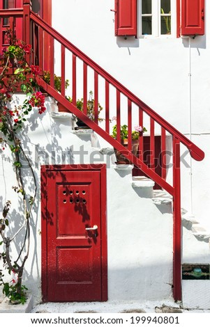 Close-up of traditional white house with red railing, door and shutters in Mykonos, Cyclades, Greece - stock photo