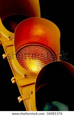 Close up of traffic light with illuminated amber lens - stock photo