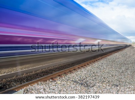 Close up of train speeding through English countryside on bright sunny day with extended exposure for extended   motion blur - stock photo
