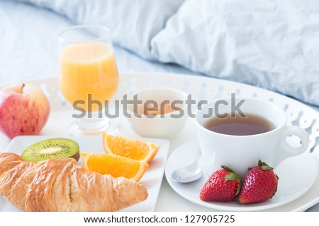Close-up of tray with tasty breakfast on a bed. - stock photo