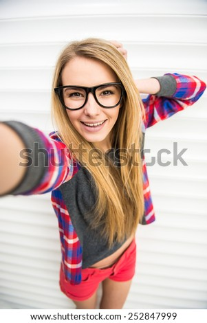 Close-up of trendy girl face in sunglasses is making selfie photo. - stock photo