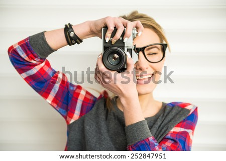 Close-up of trendy girl face in sunglasses with vintage camera. - stock photo