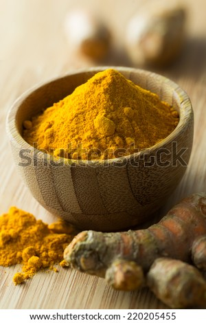 Close up of turmeric powder and turmeric on chopping board - stock photo