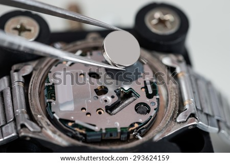 Close-up Of Tweezers Placing Battery On Silver Wrist Watch - stock photo