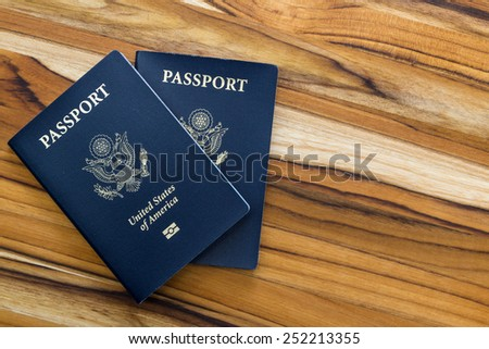 close up of two american passports on a wooden table for a travel concept - stock photo