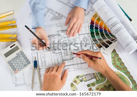 Close Up Of Two Architects Discussing Plan Together At Desk With Blueprints - stock photo