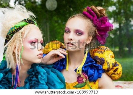 Close-up of two beautiful girls in a garden. Outdoors - stock photo
