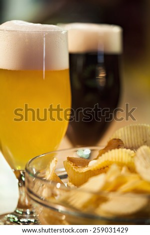 Close Up Of Two Beer Glasses And Beer Nuts - stock photo