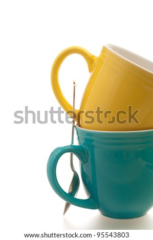 Close Up of Two Brightly Colored Coffee or Tea Mugs with a Standing Spoon On White with Room for Text or Copy