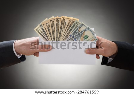 Close-up Of Two Businessman's Hand Holding Envelop Full Of Currency Note - stock photo
