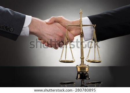 Close-up Of Two Businessman Shaking Hands In Front Of Scale - stock photo