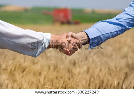Close up of two businessmen shaking hands on the farmland. Combine harvester working in background - stock photo