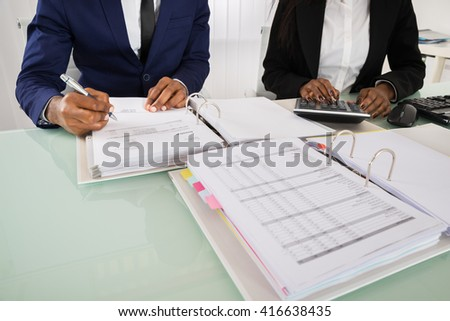 Close-up Of Two Businesspeople Calculating Invoice With Calculator At Desk - stock photo