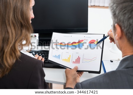 Close-up Of Two Businesspeople Discussing Graph In Office - stock photo
