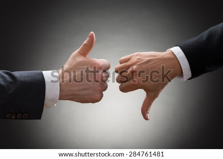 Close-up Of Two Businesspeople Hands Showing Thumb Up And Thumb Down Sign - stock photo
