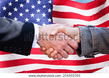 Close-up Of Two Businesspeople Shaking Hands In Front Of American Flag