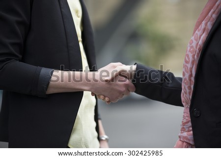Close up of two Caucasian business women shaking hands. - stock photo