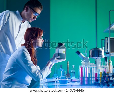 close-up of two caucasian scientists looking at a toxic waste plastic container, in a chemistry laboratory