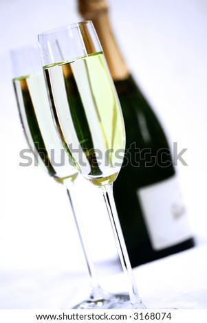 Close up of two champagne flutes and a bottle of champagne. - stock photo