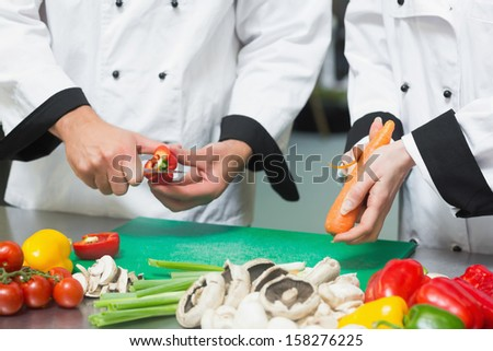 Close up of two chefs preparing vegetables in commercial kitchen