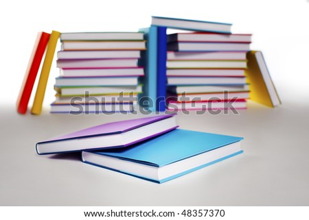 Close-up of two closed books with blank covers in front of stack in rainbow colors paper wrapped books on white background,  PHOTOGRAPH, NOT 3D RENDER.