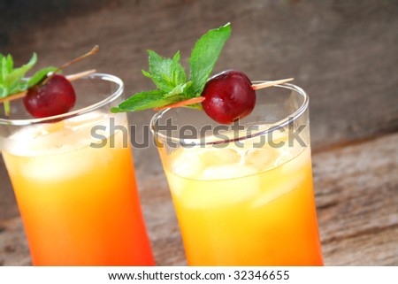 Close up of two cocktails garnished with mint leaves and fresh cherries. - stock photo