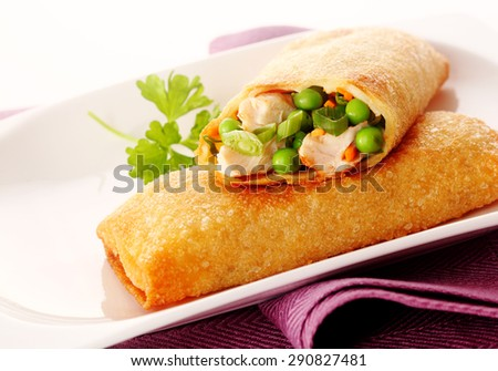 Close Up of Two Crisp Fried Spring Rolls Filled with Fresh Vegetables on White Dish with Garnish and Purple Napkin - stock photo