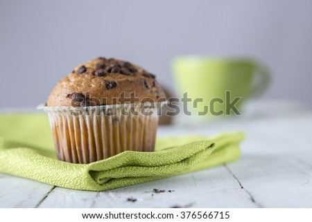 Close-up of two cupcakes decorated with chocolate chips  Green cup on background