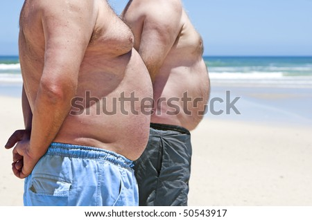 Close up of two fat men showing their bellies on the beach - stock photo