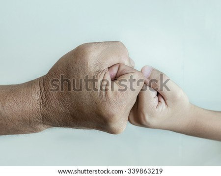 close up of two fists of adult and kids are hitting. Boxing concept. - stock photo