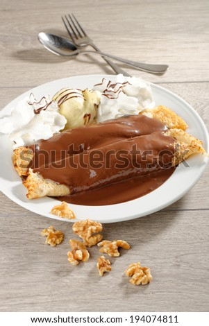 close up of two french style crepes, served with chocolate, walnuts and ice cream, shallow dof. - stock photo
