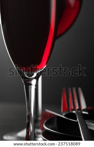 Close-up of two glass of red wine, plates and silverware on dark wooden table. Shallow DOF. - stock photo
