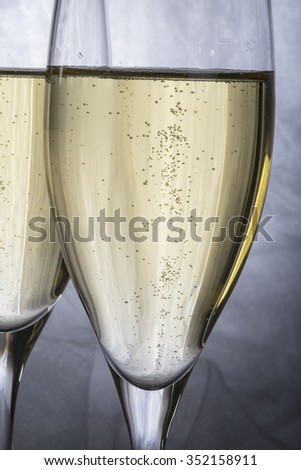 Close Up of Two Glasses of Champagne with Grey Background - stock photo