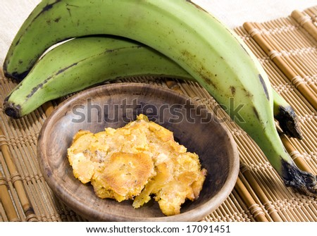 Close up of two green bananas with a wooden dish of fried slices. Focus on first banana and dish. - stock photo
