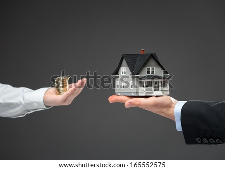Close up of two hands. One with coin money, another one with little house. Concept of deal and real estate - stock photo