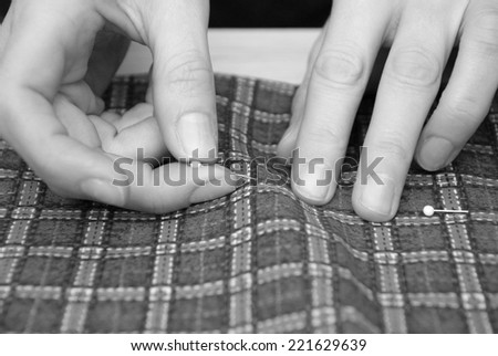 Close up of two hands pinning plaid fabric - monochrome processing