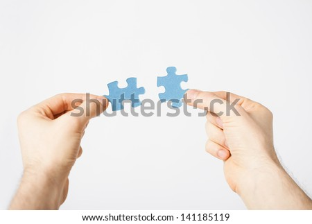 close up of two hands trying to connect puzzle pieces - stock photo