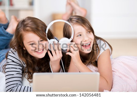 Close-up of two happy young teenage girls sharing headphones connected to a laptop to listen to music while laying on the living-room floor - stock photo