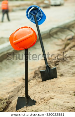Close up of two helmets hanging on shovels - stock photo