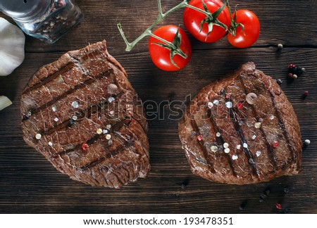 Close up of two juicy thick portions of delicious roasted or grilled beef steak with herbs, peppercorns and spices served on a wooden board with cherry tomatoes in a country kitchen - stock photo