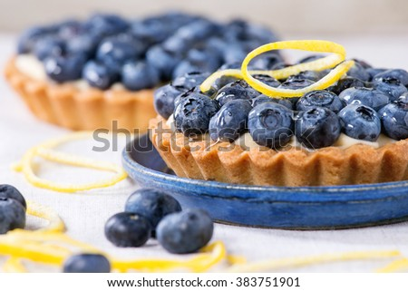 Close up of Two Lemon tartlets with fresh blueberries, served on blue ceramic plate over white textile background. - stock photo