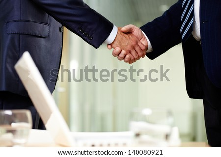 Close-up of two men handshaking after making agreement - stock photo