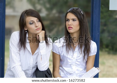 close up of two nice brunette sitting down outdoor at the bus stop - stock photo
