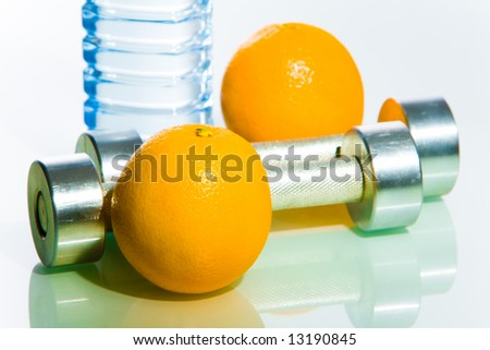 Close-up of two oranges with two barbells between on the background of bottle with water - stock photo
