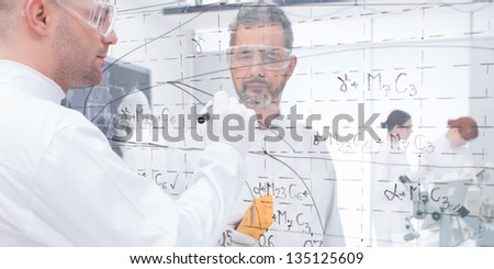 close-up of two people in a chemistry lab on both sides of a transparent board pointing and analyzing formulas on it - stock photo