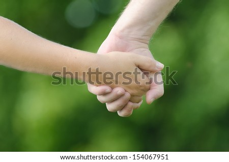 Close-up of two people (man and woman) holding hands on green background. A symbol of love, connection, closeness, relationship and friendship. Natural lightning of summer time. - stock photo