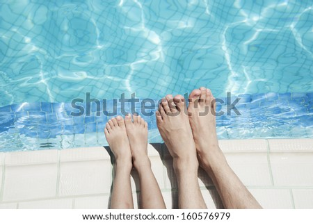 Close up of two people's legs by pool side - stock photo