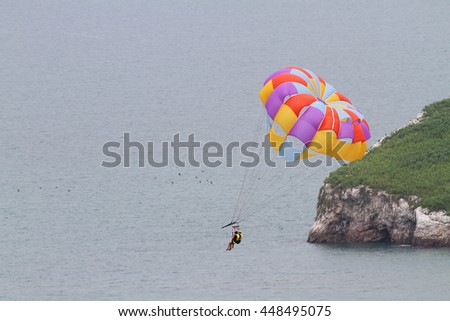 Close up of two persons on a Parasailing boat ride over the ocean going over an island - stock photo
